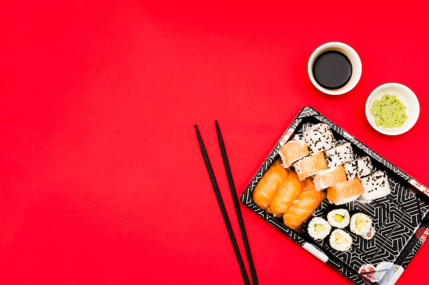 An elevated view of tray filled with tasty rolls near wasabi and soy sauce in bowl on red surface Premium Photo