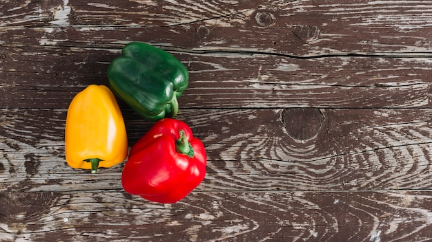 An elevated view of tri color organic bell peppers on wooden desk Free Photo