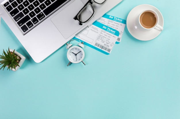 An elevated view of two air tickets with coffee cup,laptop,eyeglasses,alarm clock on blue office desk Free Photo