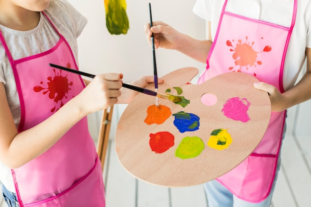 An elevated view of two girls in same pink apron mixing the paint on wooden palette with paint brush Free Photo