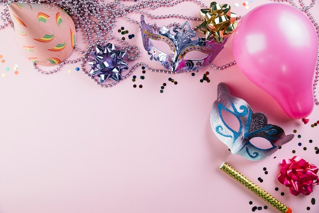 Elevated view of two masquerade carnival mask with party decoration material over pink background Free Photo