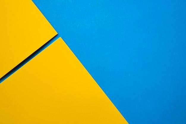 Una vista elevata di due craftpapers gialli sulla superficie del blu Foto Gratuite