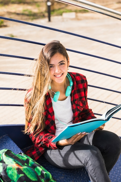 An elevated view of university student sitting on staircase holding book in hand Free Photo