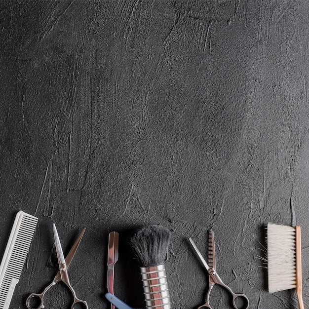 Elevated view of various barber tools on black background Free Photo
