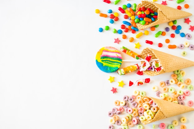 Elevated view of various colorful candies with waffle ice cream cone on white surface Free Photo