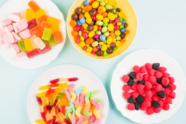 Elevated view of various sweet candies on plate over colored background Free Photo