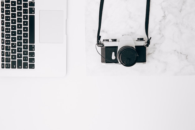 An elevated view of vintage camera and laptop on white desk Free Photo