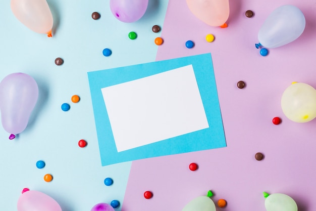 An elevated view of white and blue paper surrounded with gems and balloons on blue and pink backdrop Free Photo