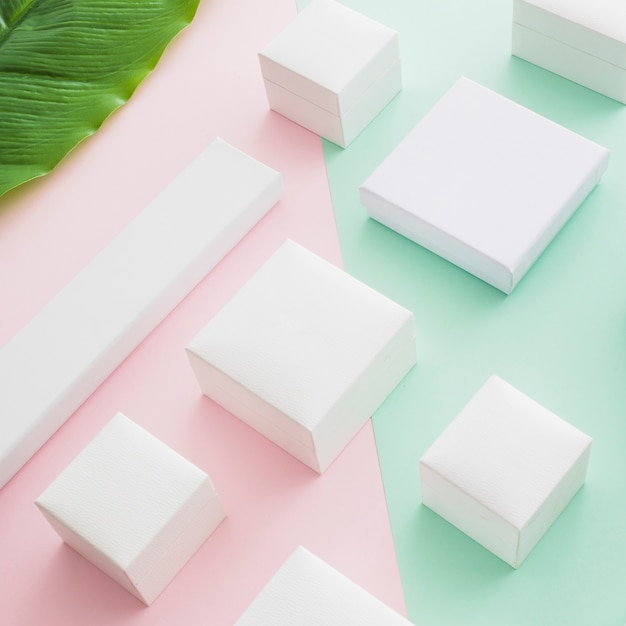 Elevated view of white boxes on colored paper backdrop Free Photo