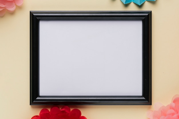 Elevated view of white empty frame on beige backdrop Free Photo