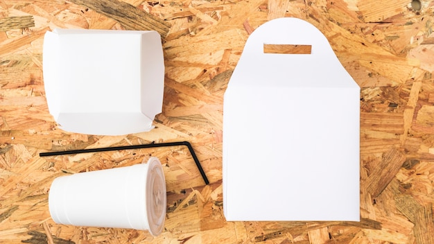 An elevated view of white takeaway food on wooden background Free Photo
