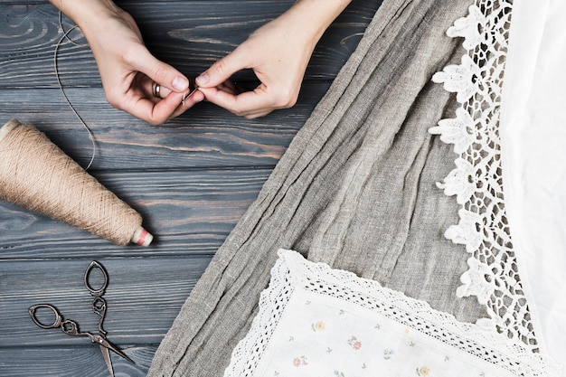 Elevated view of a woman inserting thread into the needle near textiles over wooden table Free Photo