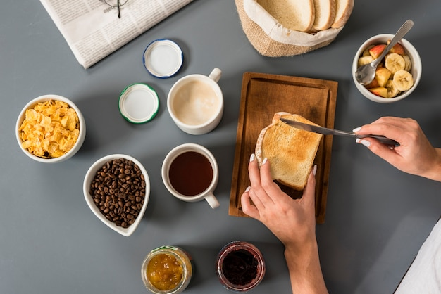 An elevated view of woman's hand having breakfast Free Photo