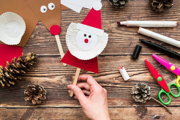 An elevated view of woman's hand holding santa claus prop over the table Free Photo