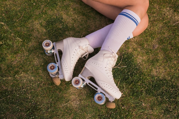An elevated view of woman's leg wearing white vintage roller skate lying on green grass Free Photo
