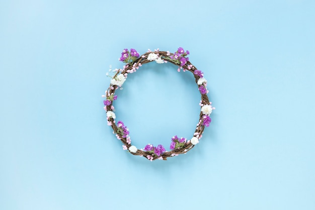 Elevated view of wreath made up of flowers on blue backdrop Free Photo