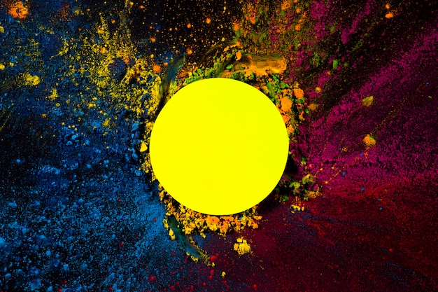 Elevated view of yellow circular frame covered with dry holi colors Free Photo