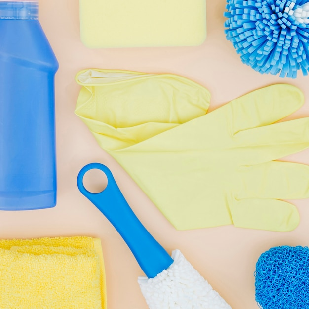 An elevated view of yellow gloves; sponge; bottle; napkin on peach backdrop Free Photo