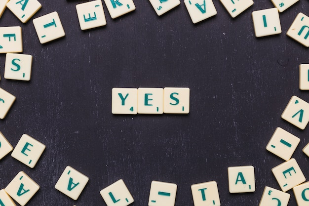 Elevated view of yes word made from game scrabble letters Free Photo