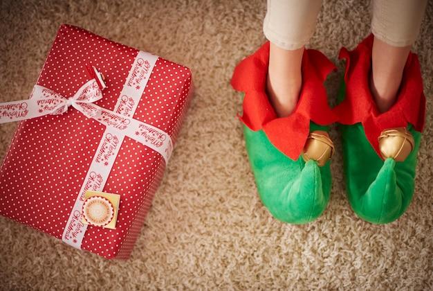 Gambe di elfi accanto al regalo di natale Foto Gratuite