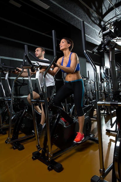 Elliptical walker trainer man and woman at black gym Premium Photo
