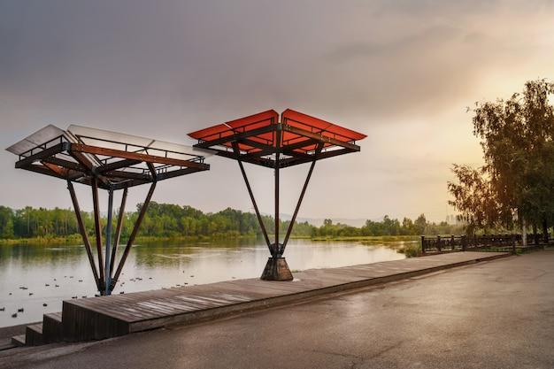 クラスノヤルスクのエニセイ川の堤防。美しい展望台と天蓋付きのベランダ。堤防の配置。アーバンデザイン。造園と風景の美しい夕景。 Premium写真