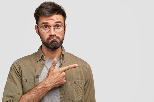 Embarrassed bearded male purses lips and looks with bewilderment, points aside with index finger Free Photo