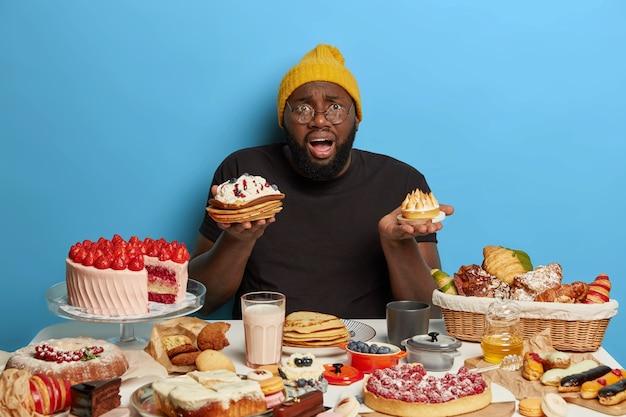 Смущенный черный толстый бородатый мужчина держит два вкусных торта, не может выбрать, что поесть, вкусный сладкий завтрак, одетый в повседневную одежду, изолированный на синей стене. Бесплатные Фотографии