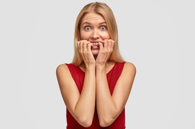 恥ずかしい金髪女性が指の爪を噛み、意外と心配そうな表情で 無料写真