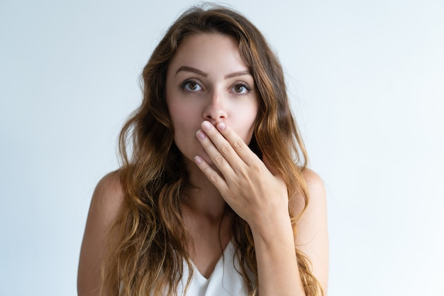 Embarrassed pretty young woman covering mouth with hand Free Photo