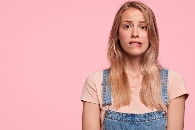 恥ずかしい困惑した素敵な女性が唇を噛み、悲惨な表情をして、ファッショナブルなデニムのオーバーオールを着ています 無料写真