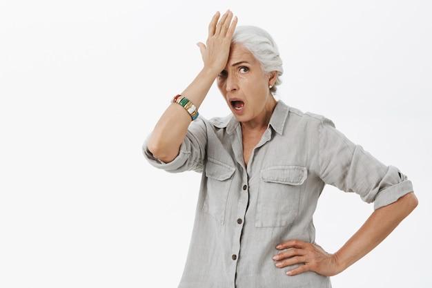 Donna maggiore imbarazzata e scioccata schiaffeggia la fronte e sembra preoccupata Foto Gratuite