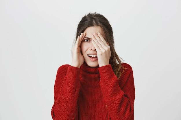 Donna imbarazzata che dà una occhiata a qualcosa di disgustoso Foto Gratuite