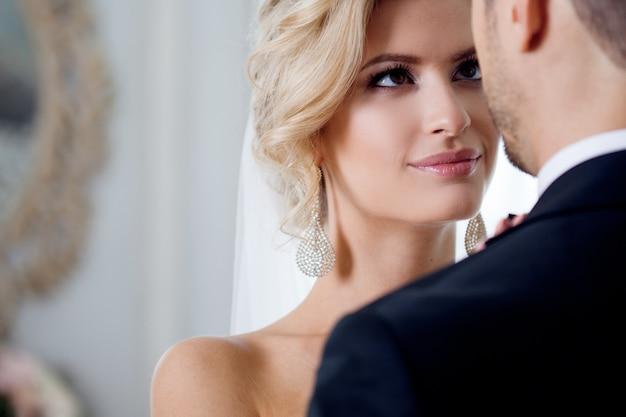 結婚式の日に受け入れます。首に新郎を抱きしめる美しい花嫁 Premium写真
