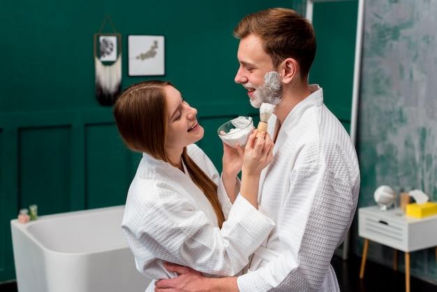 Free Photo | Embraced couple in bathrobes applying shaving foam