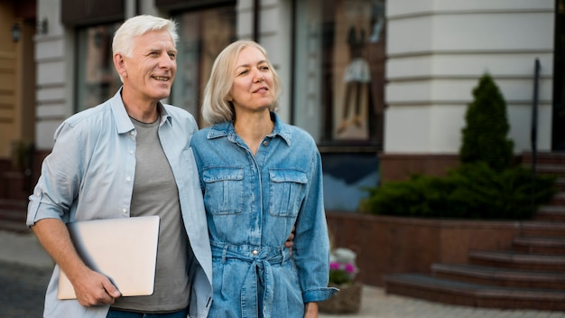 Embraced older couple outdoors in the city with tablet Premium Photo