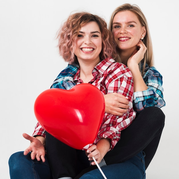 Embraced women posing with balloon for valentines Free Photo