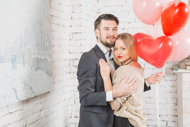 Embracing couple with bunch of balloons Free Photo