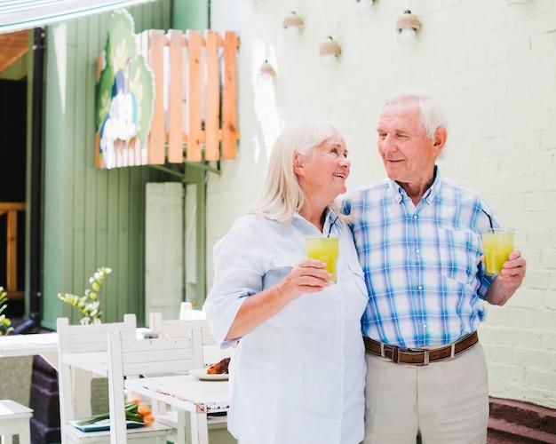 Embracing elderly couple drinking juice in cafe Free Photo