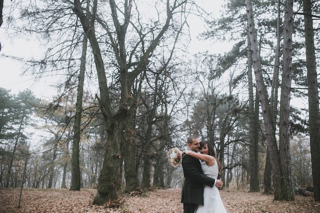 Embracing newlyweds in leafless forest Free Photo