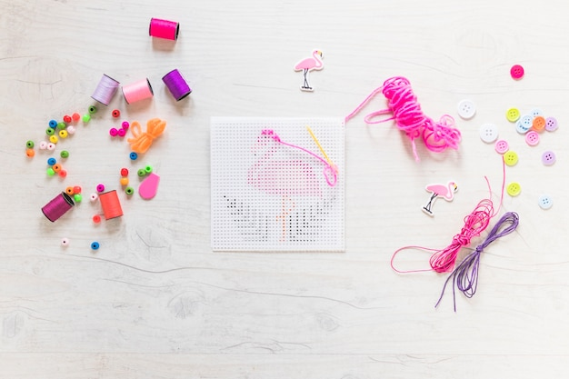 Embroidery cross-stitch with floss thread and decorative elements on textured backdrop Free Photo