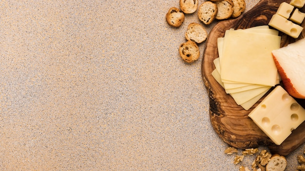 Emmental cheese and gouda cheese with slices on coaster with bread slices and walnut over beige textured backdrop Free Photo