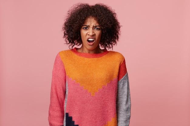 ひどいひどい恐ろしい嫌な何かを見ているアフロの髪型を持つ感情的なアフリカ系アメリカ人の女性は、彼女の顔を眉をひそめ、カラフルなセーターを着て、孤立している 無料写真