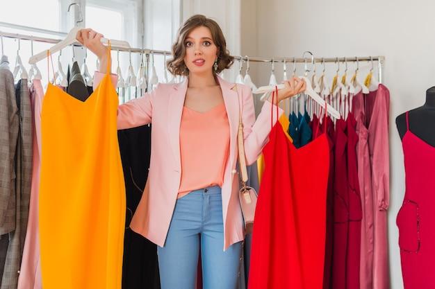 Эмоциональная привлекательная счастливая женщина, держащая красочные платья в магазине одежды Бесплатные Фотографии