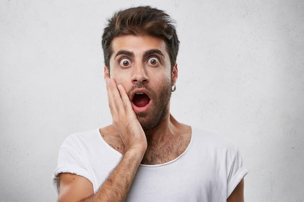 Эмоциональный бородатый парень, держащий руку на щеке, с выпученными глазами и открытым ртом, испуганный во время просмотра фильма ужасов. молодой человек со страшным взглядом Бесплатные Фотографии