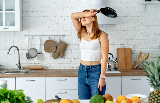 The emotional and beautiful woman prepares food in a frying pan in the kitchen Premium Photo