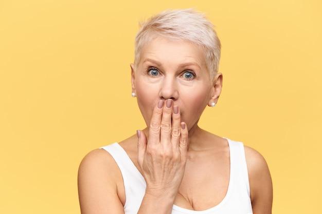 Emotiva bionda donna di mezza età che spalanca gli occhi e copre la bocca con la mano, cercando di non rivelare informazioni intriganti o segreti, avendo sorpreso l'espressione del viso stupita Foto Gratuite