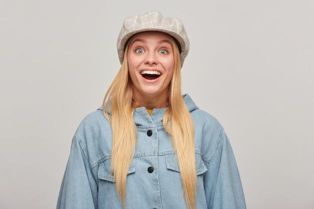 Эмоциональная блондинка молодая женщина с распущенными волосами, выглядящая неожиданно обрадованной Бесплатные Фотографии