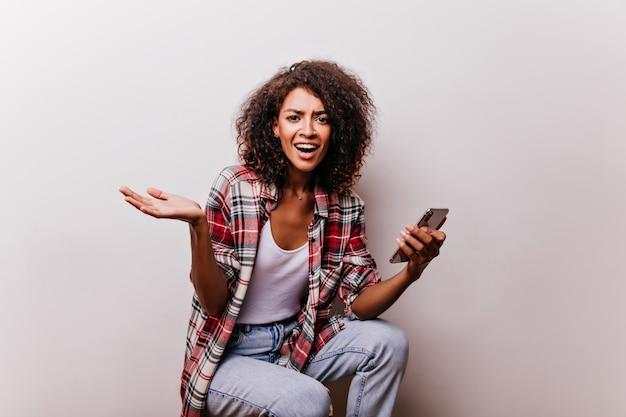 スマートフォンを保持している感情的なブルネットの女性。彼女の手にデバイスを持ってポーズをとる素晴らしいアフリカの女の子。 無料写真