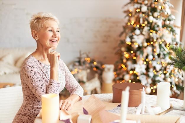 クリスマスの準備をクラフト紙で包み、幸せな大喜びの表情を持ち、家族や友人への贈り物を作るピクシーヘアスタイルの感情的に魅力的な引退した女性 無料写真